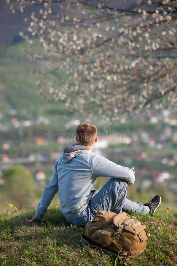 Traveler young man with backpack on hill. Man with a backpack sitting under a blossoming tree on top of hill with green grass and yellow wildflowers and enjoying royalty free stock image