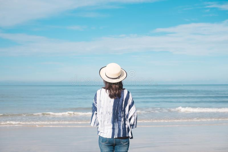 traveler young woman in casual dress with hat stand alone on beach has blue sky and sea background stock photography