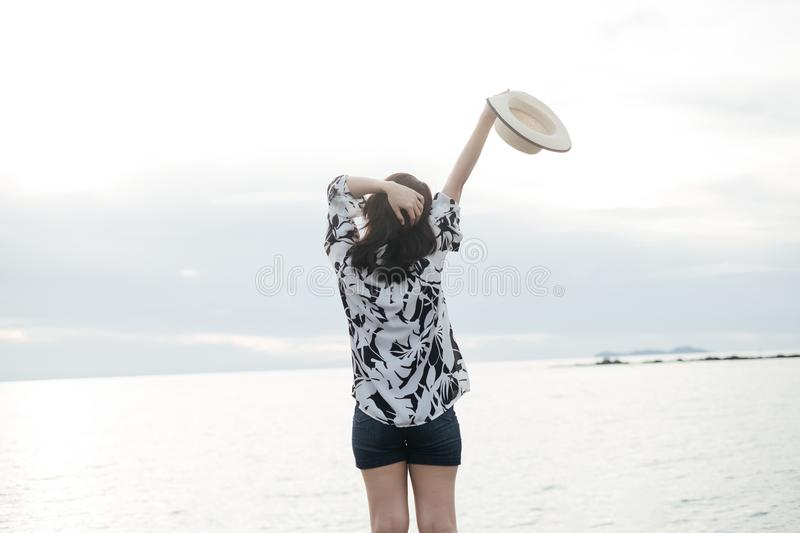 traveler young woman in casual dress with hat stand alone on beach has sea background royalty free stock photography