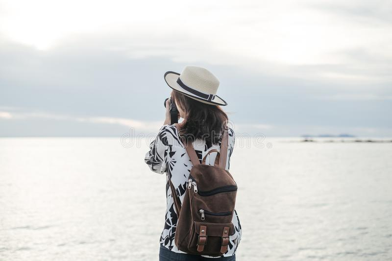 traveler young woman in casual dress holding camera and take photo with backpack stand alone on beach has sea background royalty free stock images