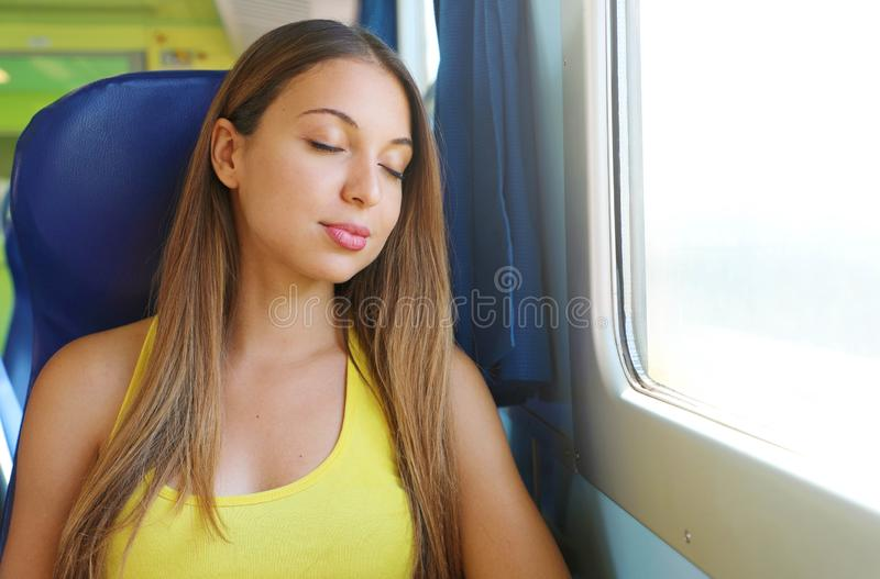 Traveler young woman sleeping in a train travels beside the window. Tired sexy lady take a nap. Girl sitting on seat on train or royalty free stock photography
