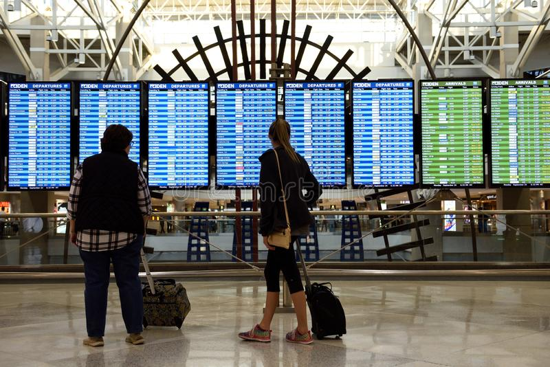 Travelers checking the flight arrival and departures information schedule display screens stock photo