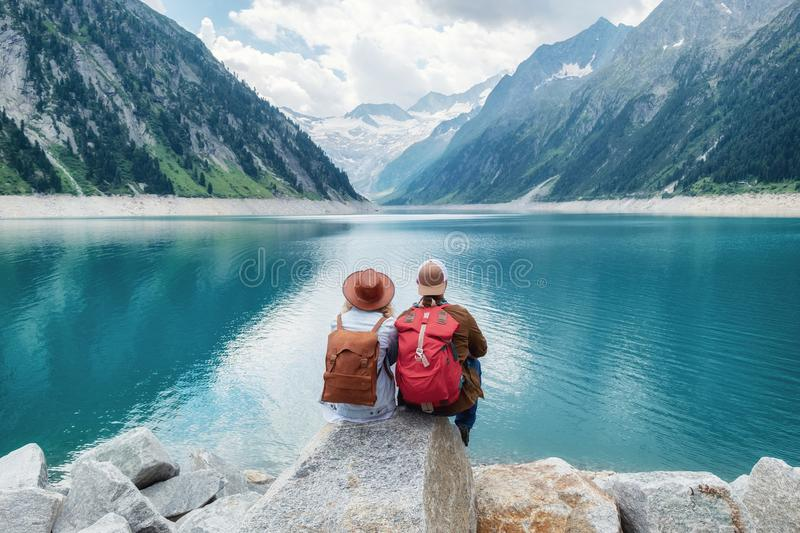 Travelers couple look at the mountain lake. Travel and active life concept with team. Adventure and travel in the mountains region in the Austria royalty free stock photography