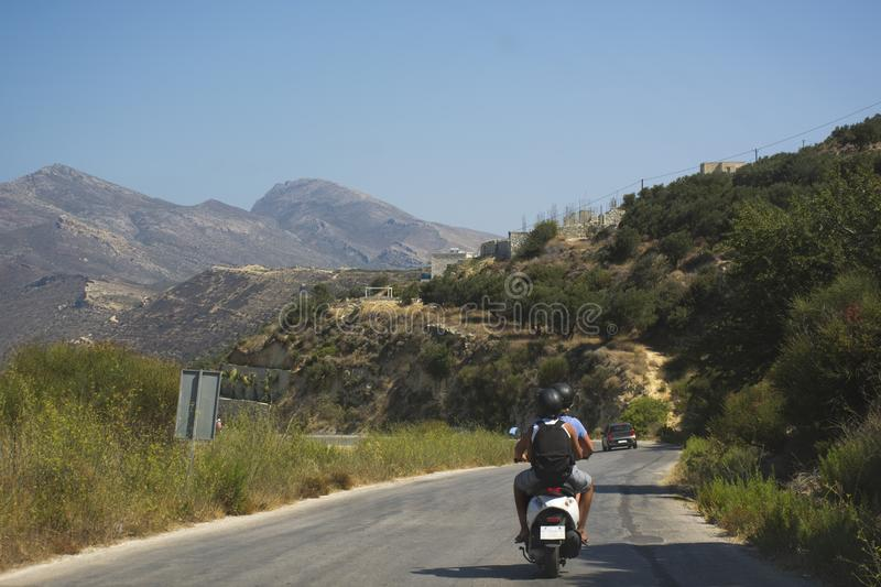 Travelers couple on scooter riding a mountain road. Crete island, Greece stock image