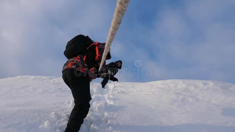 Travelers descend by rope from snowy hill. Alpinists team in winter down rope from the mountain. well-coordinated. Travelers descend by rope from snowy hill stock photography