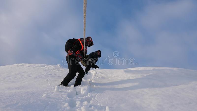 Travelers descend by rope from snowy hill. Alpinists team in winter down rope from the mountain. well-coordinated. Travelers descend by rope from snowy hill royalty free stock photo