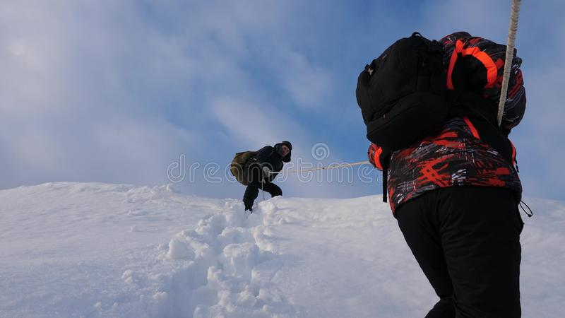 Travelers descend by rope from snowy hill. Alpinists team in winter down rope from the mountain. well-coordinated. Travelers descend by rope from snowy hill stock photo