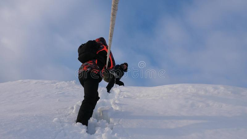 Travelers descend by rope from snowy hill. Alpinists team in winter down rope from the mountain. well-coordinated. Travelers descend by rope from snowy hill royalty free stock image