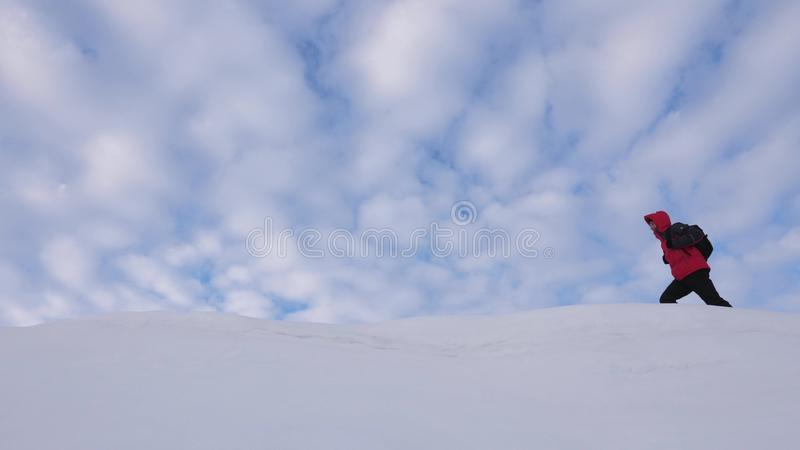Travelers follow one another along snowy ridge. Alpenists team in winter go to top of the mountain. well-coordinated royalty free stock photo
