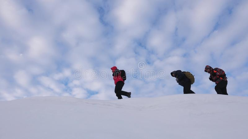 Travelers follow one another along snowy ridge. Alpenists team in winter go to top of the mountain. well-coordinated stock photography