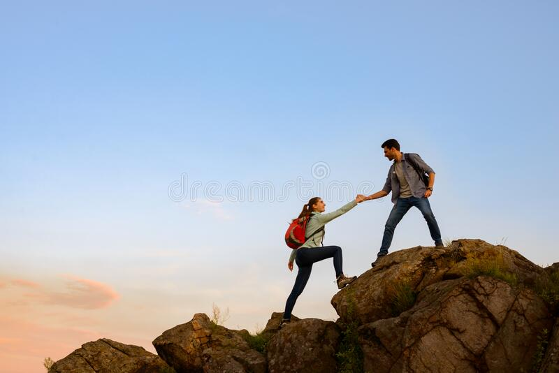 Travelers Hiking in the Mountains at Sunset. Man Helping Woman to Climb to the Top. Family Travel and Adventure. royalty free stock image