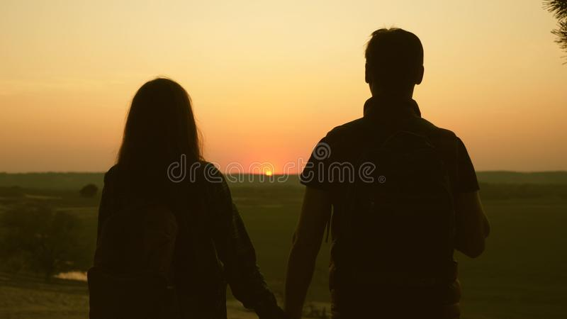 Travelers Man and woman raise their hands to sun and enjoy sunset. Teamwork travelers with backpacks. Family of tourists. Travelers Man and woman raise their stock images