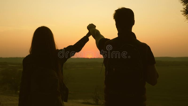 Travelers Man and woman raise their hands to sun and enjoy sunset. Teamwork travelers with backpacks. Family of tourists. Travelers Man and women raise their stock photo