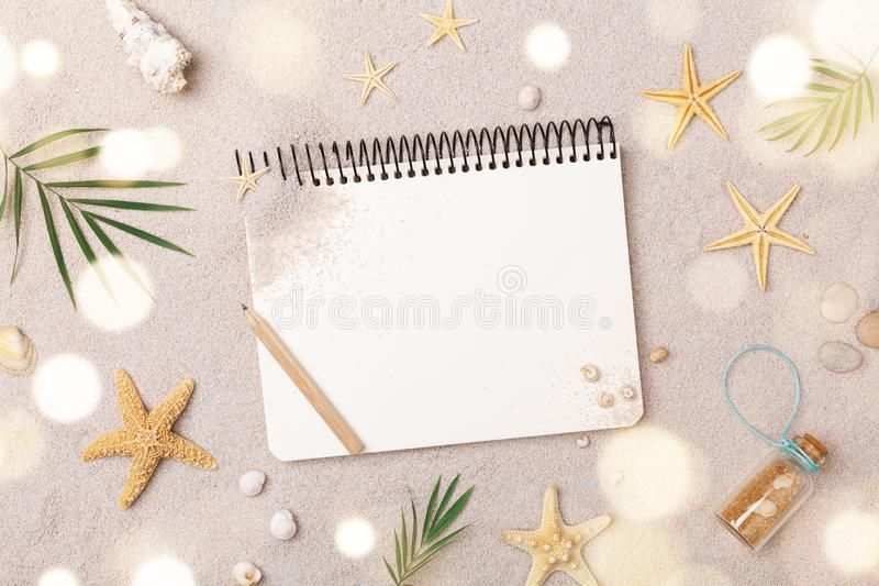Travelers notebook with accessories on sand background top view. Planning summer holidays, trip and vacation concept. Flat lay. Style stock image