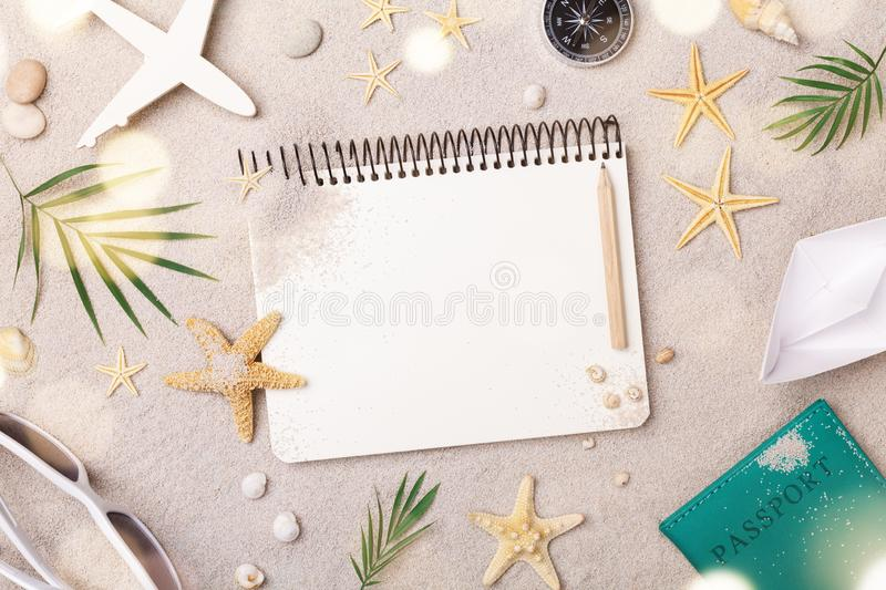Travelers notebook with accessories on sand background top view. Planning summer holidays, trip and vacation concept. Flat lay. Style royalty free stock photo