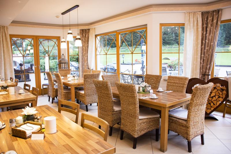 Travelers people use and eating breakfast in comfortable restaurant. Room of resort hotel at Pfunds city with grass field and mountain in morning time and stock photography