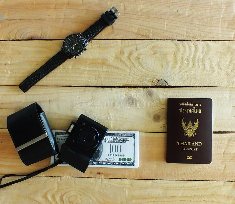 The compact cameras on desk. Travelers prepare before traveling abroad. Prepare passports, banknotes, wrist watches and compact cameras royalty free stock photography