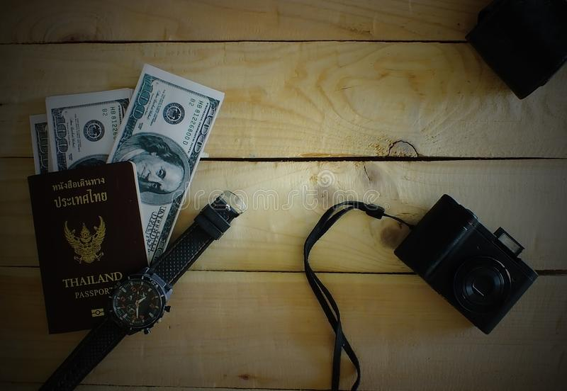 Wrist watches, compact cameras.Dark edges. Travelers prepare before traveling abroad. Prepare passports, banknotes, wrist watches, compact cameras.Dark edges royalty free stock images