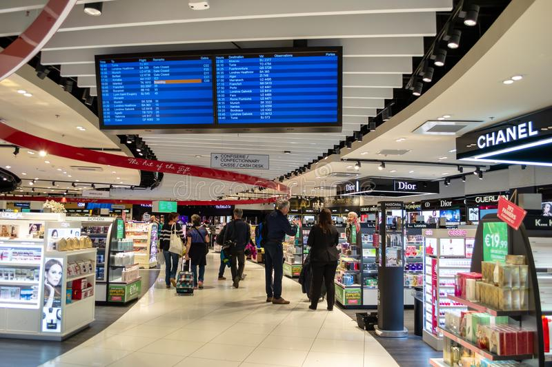 Travelers in Saint Exupery airport, Lyon, moving through the isles of a duty free shop inside the terminals. Lyon, France - 16 March 2019: Travelers in Saint stock photo