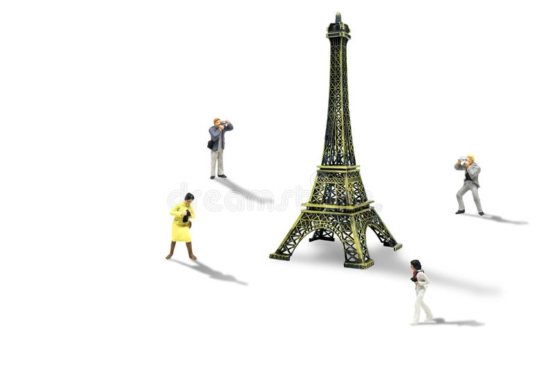 Travelers taking photograph Eiffel Tower model isolated on white background. Vacation and Holiday Trip Concept : Miniature figurine character as travelers royalty free stock photo