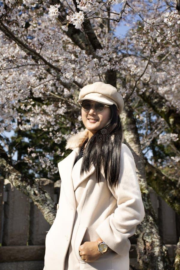 Travelers thai women walking and posing portrait for take photo with Sakura tree in Naritasan plum garden at Chiba in Tokyo, Japan royalty free stock images