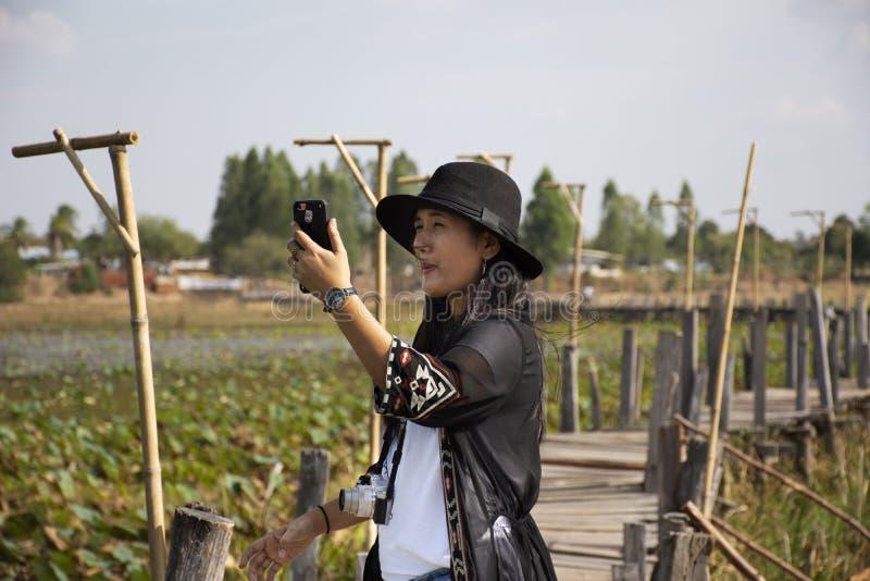 Thai women people travel visit and posing portrait for take photo on Kae Dam long wood bridge in Maha Sarakham Province, Thailand. Travelers thai woman people stock photos