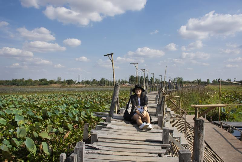 Thai women people travel visit and posing portrait for take photo on Kae Dam long wood bridge in Maha Sarakham Province, Thailand. Travelers thai woman people royalty free stock image
