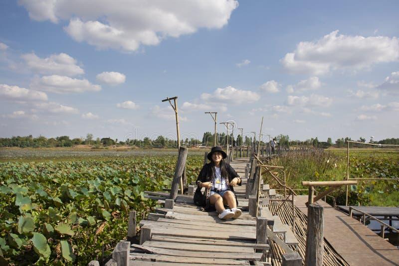 Thai women people travel visit and posing portrait for take photo on Kae Dam long wood bridge in Maha Sarakham Province, Thailand. Travelers thai woman people stock photo