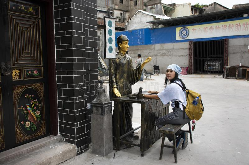 Thai women visit and posing for take photo with fortune teller statue in small alley at Shantou or Swatow in Guangdong, China royalty free stock photography