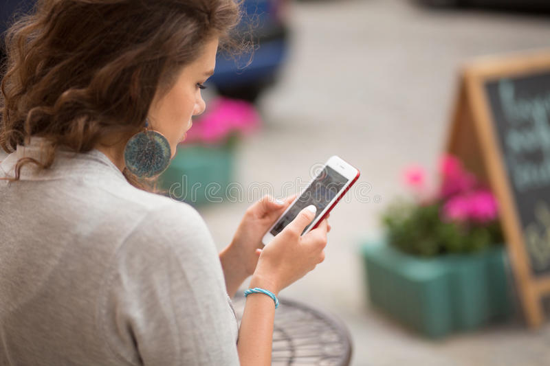Travelgirl looking at photos taken on phone camera. Side view on a young woman sitting in the street cafe with smartphone in her hands royalty free stock photography