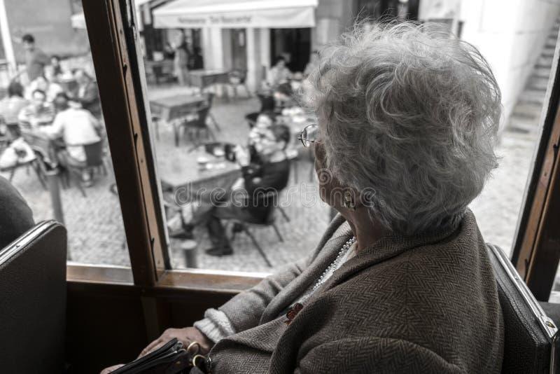 Travelig de la mujer mayor en una tranvía del vintage en Lisboa alrededor de Alfama fotografía de archivo