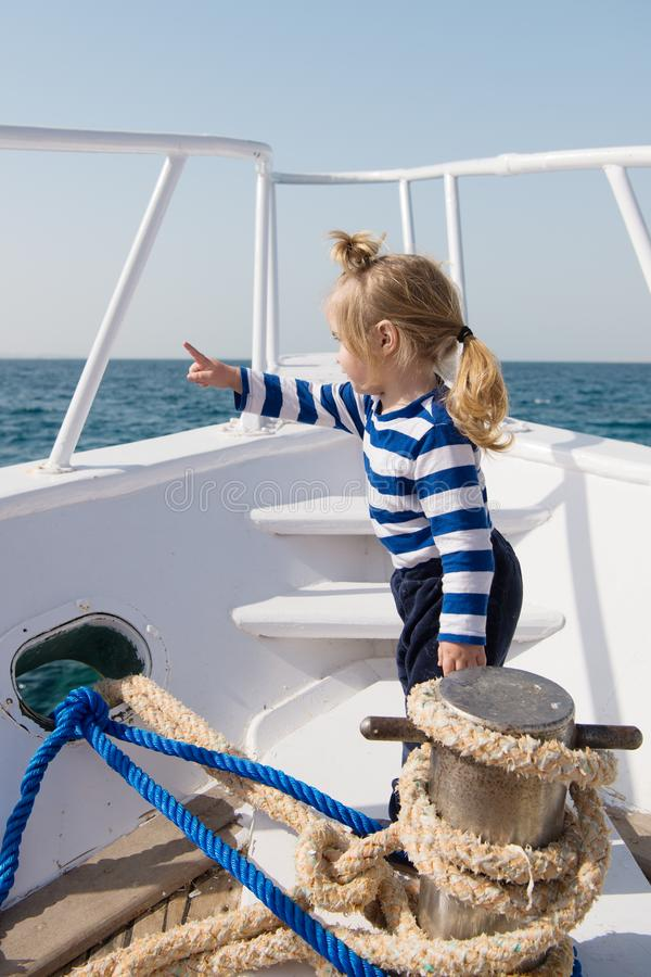 Traveling adventures and wanderlust. funny kid in striped marine shirt. happy little boy on yacht. boat trip by sea royalty free stock image