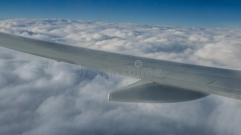 Traveling by air. Plane wing in flight. Beautiful sky and wonderful clouds royalty free stock image