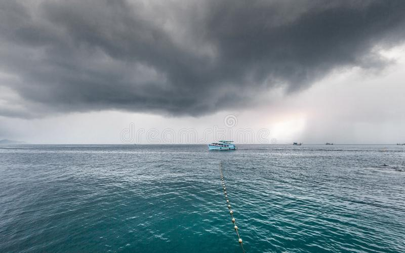 Traveling boat with passenger go to island while raining strom near comes royalty free stock photo