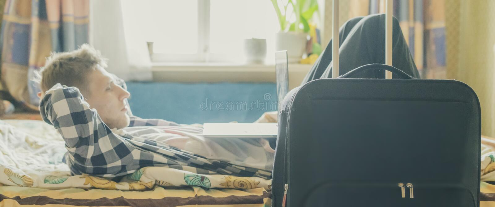 Traveling businessman have a rest in the hotel room, lying in the bed next to the luggage f. Traveling businessman have a rest in the hotel room, lying in the royalty free stock image