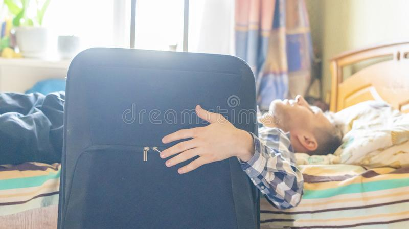 Traveling businessman have a rest in the hotel room, lying in the bed next to the luggage f. Traveling businessman have a rest in the hotel room, lying in the royalty free stock photos