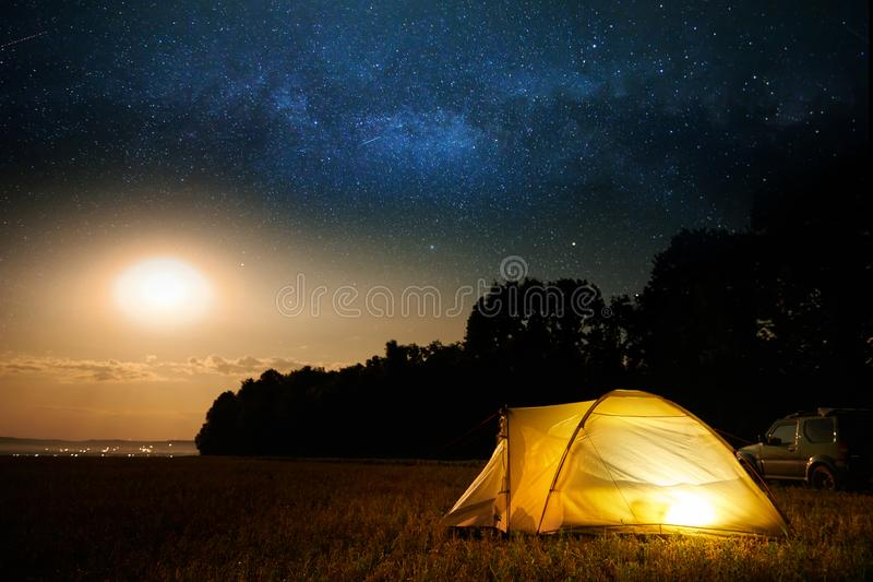Traveling and camping concept - camp tent at night under a sky full of stars. Orange illuminated tent and car. Beautiful nature - royalty free stock photography