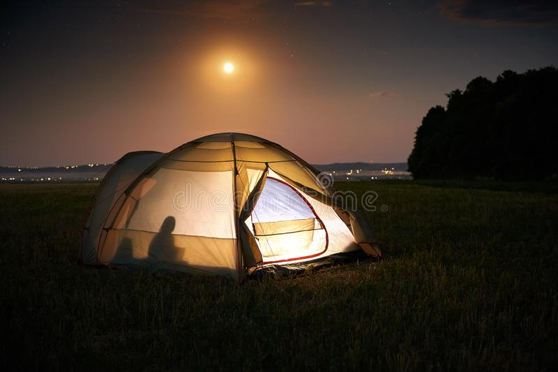 Traveling and camping concept - camp tent at night under a sky full of stars. Orange illuminated tent with a person inside. royalty free stock photos