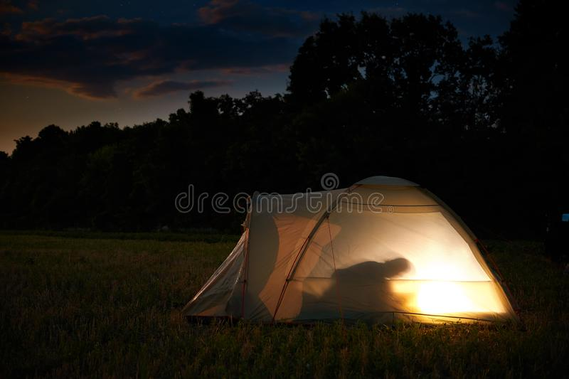 Traveling and camping concept - camp tent at night under a sky full of stars. Orange illuminated tent with a person inside. stock images