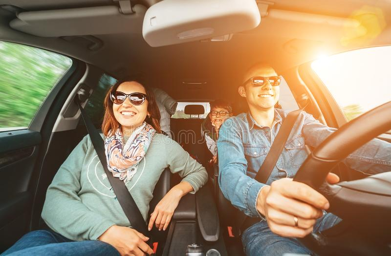 Young traditional family has a long auto journey and Cheerfully singing aloud the favorite song together. Safety riding car concep. T wide angle inside car view stock photos