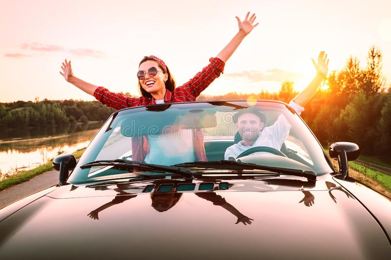 Traveling by car - happy couple in love go by cabriolet car in sunset time royalty free stock photo