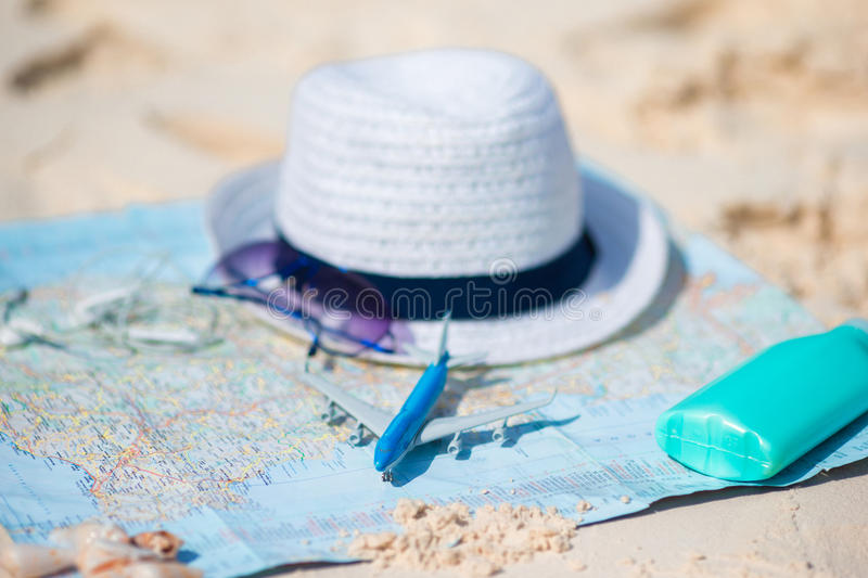 Traveling concept. Hat, suncream, sunglasses on a map of the world. Closeup of passports, toy airplane, sunglasses on the map royalty free stock photo