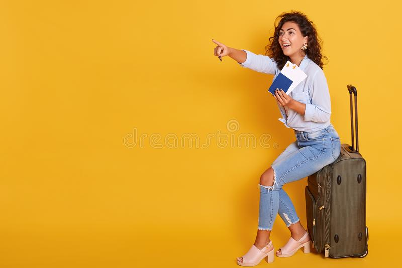 Traveling Concept. Portrait of cheerful exited young caucasian woman, dressed casual clothing, holding passport with flying stock photo