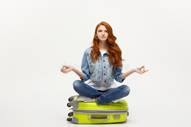 Traveling concept. Young pretty ginger woman meditating in lotus pose on the luggage valise. Isolated on white. royalty free stock photos