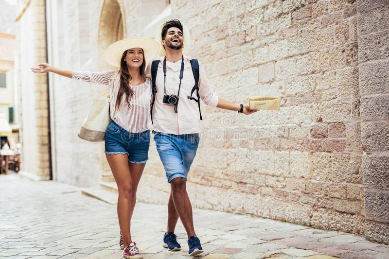Traveling couple of tourists walking around old town. royalty free stock photography