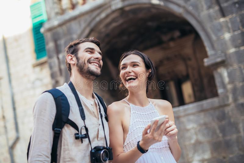 Traveling couple of tourists walking around old town, and using smart phone stock images