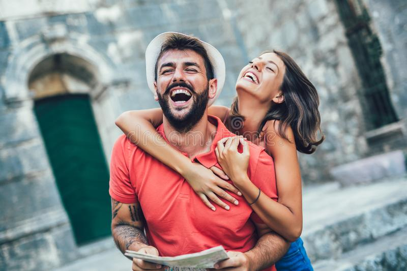 Traveling couple of tourists walking around old town. stock photo