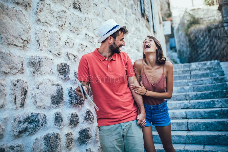 Traveling couple of tourists walking around old town. royalty free stock image