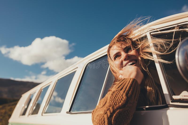 Traveling female driving the van and enjoying road trip royalty free stock images