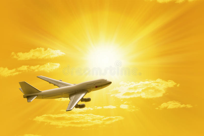 Traveling Flying Airplane Sunset Sky. An airplane flying through a yellow sky with the sun and clouds in the background royalty free stock images